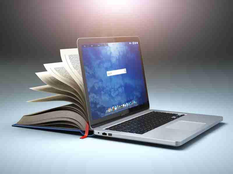 livro entre aberto fazendo paralelo com um laptop semi-aberto