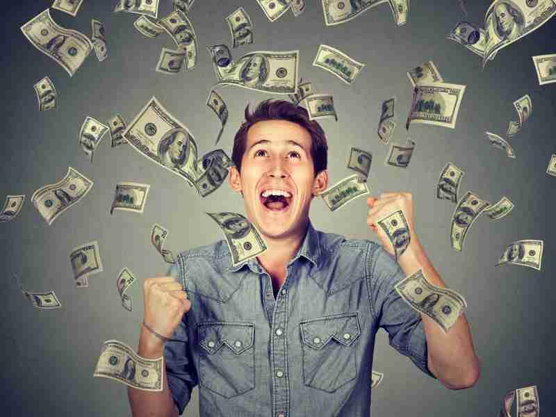 rapaz comemorando enquanto caem cédulas de dinheiro