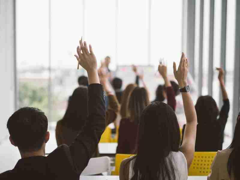 alunos sentados erguendo a mão